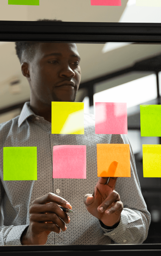 A productive employee busy sticking sticky notes onto a glass wall.