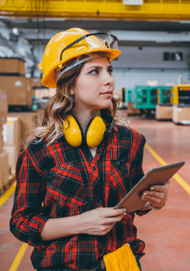 A woman standing in a factory, wearing a yellow hardhat and earmuffs, carrying a clipboard while undertaking a occupational health and safety assessment.